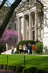 Students stroll past Schaeffer Hall framed by the expertly manicured grounds of the Pentacrest.