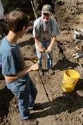 Two volunteers use probes to penetrate the surface. When the probe hits an object below, a flag is placed to mark the spot for excavation. Notice the pattern of holes created by the probe.